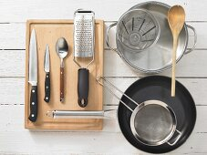 Various kitchen utensils: pot, pan, strainer, measuring cup, grater, knives, spoon