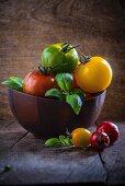 Heirloom Tomaten und Basilikum in Holzschale