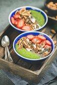 Grüne Smoothie-Bowls mit Erdbeeren, Müsli, Chia und getrockneten Feigen