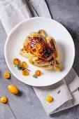 Whole roasted mini chicken cooking with caramelized kumquats served with fresh citrus fruits