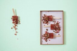Rhubarb ice lollies on sticks with a caramelised pumpkin seed and raspberry crumble