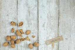 Walnuts with a brown paper label on a wooden background (top view)