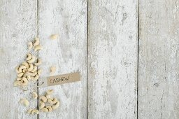 Cashew nuts with a brown paper label on a wooden background (top view)