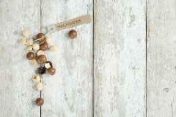 Macadamia nuts with a brown paper label on a wooden background (top view)