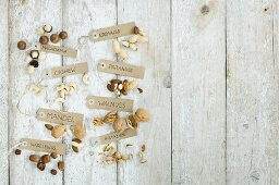 Various nuts with brown paper labels on a wooden background (top view)