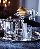 Silver tray with a silver jug, a small glass and a stack of pastries