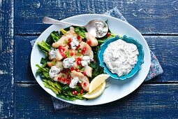 Fried cod with spinach, pomegranate and herb yogurt sauce