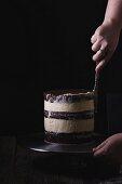 Buttercream layered wedding cake being iced