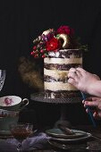 Layered wedding cake being sprinkled with gold dust