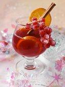 Ein Glas weihnachtlicher Fruchtpunsch mit Orangenscheiben und Zimtstange