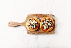 Two mini pizzas with spinach and garlic on a kitchen board