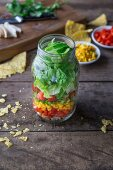 Layered salad with chicken breast, red pepper, sweetcorn, romaine lettuce, tomato and tortilla chips