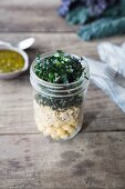 Layered salad with brown rice, chickpeas, palm kale and pesto