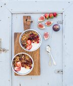 Bowls of oat granola with yogurt, fresh strawberries, figs, pomegranate and honey on rustic wooden board