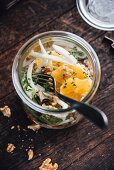 Salad with white cabbage, carrots, green salad, fennel, orange and walnuts in a jar, vegan