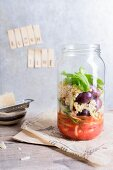 Quinoa salad with tomatoes, mozzarella and basil in a glass jar