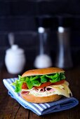 A bagel with cream cheese, cooked ham, cheese, tomato and salad
