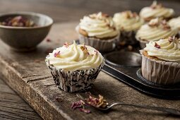 Rose and lemon cupcakes with rosewater and lemon frosting in a rustic baking tin decorated with dried edible rose petals with spoon and bowl of rose petals on a wooden board and table