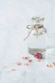 Clear glass bottle of rosewater tied with string on a white and grey marble surface with dried pink edible rose petals