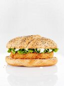 A chicken burger with mayo and salad