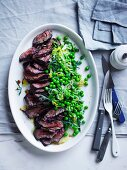 A hanger steak with pepper, peas and lettuce