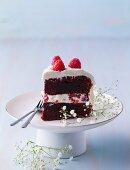 Ein Stück Red Velvet Torte mit Himbeeren auf Kuchenständer