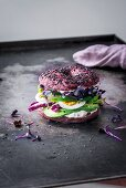 A beetroot bagel with spelt, black sesame, avocado, radicchio, egg, sakura curry, green peppers and fresh cheese