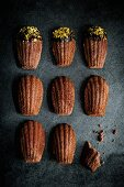Chocolate madeleines with a chocolate glaze and pistachio crumbs (top view)
