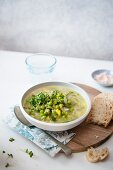 Spring vegetable soup with a piece of bread