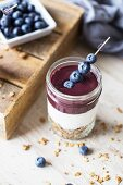 Layered granola, yoghurt and acai puree, garnished with blueberries