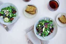 Bowls of Spicy Pecans Feta Arugula Salad served with bread and red wine