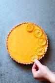 Female hand decorating a lemon tart with lemon slices