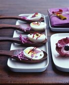 Half boiled eggs with red cabbage on wooden spoons