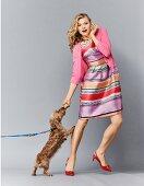 Blonde Frau in bunt gestreiftem Kleid, pinkfarbenem Cardigan und Slingback-Pumps mit einem Hund