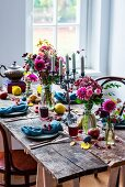 Rustic arrangement of flowers and fruit on set wooden table