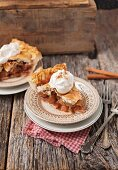 Slice of double crust apple pie with whipped cream and cinnamon on a rustic wooden surface