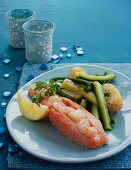 A salmon fillet with shrimps, potatoes and zucchini strips