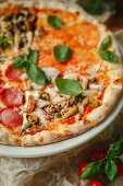 Pizza Quattro Stagioni with salami, seafood, tomatoes and mushrooms