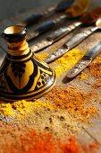 Verschiedene Gewürze und Mohn auf Tisch mit orientalischem Geschirr