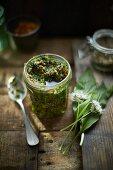 Wild garlic pesto on wood in a jar
