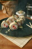 Sushi rolls with salmon, deep fried in tempura batter, on a black plate