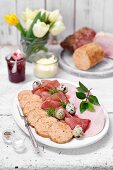 A ham and sausage platter with quail eggs for Easter brunch