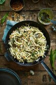 Spaghetti in a pan with wild garlic pesto (seen from above)