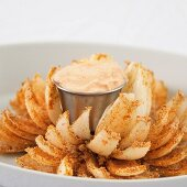 A baked onion arranged like a flower with a dip