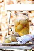 A small pear cake in a glass jar with a jar of pickled lemons