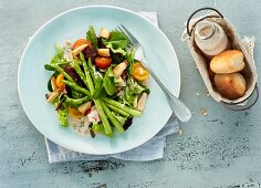 A fresh summer salad with green baby asparagus and pizza bread