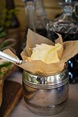 Softened butter with paper in a silver barrel