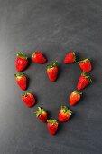 Strawberries arranged in a heart shape on a blackboard
