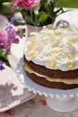 Summery lemon curd drizzle cake with coconut on a cake stand