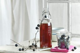 Blackthorn syrup in a bottle, blackthorn fruits in a storage jar and a blackthorn branch and label
